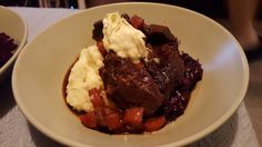 Ale-braised ox cheek with mash, red cabbage and English mustard clotted cream