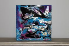 This unique painting was created using epoxy resin to give a glossy, glass like finish that enhances the colors and provides a 3 dimensional effect. This colorful painting would make a vibrant additional in any space.  Colors - blue, purple, black, white, gray Dimensions - 10 inch by 10 inch Depth - 2 inches thick Material - Wooden panel, epoxy resin, acrylic, ink Side - finished with black paint  Signed on front of the painting.  *** Id be happy to make something similar or a pair or set…