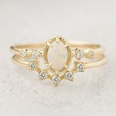 Beautiful and unique Australian Opal engagement ring featuring 6x4mm white-blueish opal paired with a diamond curved band with star shape setting. Perfect choice for women who wants a unique and different ring than an ordinary engagement ring. The set is offered in 14k solid yellow