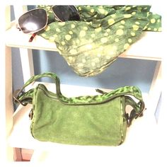"Green Suede DKNY Handbag - EUC Bright green suede handbag with green leather animal print accents. Side buckles, adjustable shoulder strap, with inside zippered pocket. Used once, plastic still on inside brand plate. A few minor marks that were present when I purchased and reflected in price. 9"" wide by 5"" tall by 4.5"" deep. Shoulder strap from seam to seam is 19"" when adjusted to the middle buckle hole. From a pet free and smoke free environment. Gorgeous bag and a perfect color for spring…"