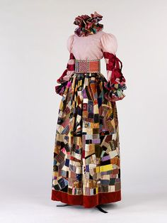 """Evening Ensemble designed by Adolfo, 1967  """"Adolfo was known for his extravagant patchwork evening looks. In this outfit he recycled an antique crazy-patchwork quilt to make the skirt, neck ruff and wrist ruffles. He treated the historic textile with respect, gathering rather than cutting it to make the skirt."""""""
