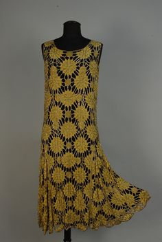"873 FRENCH CUTWORK CHIFFON and SILVER BEADED FLAPPER DRESS Sleeveless lemon yellow chiffon in an openwork chrysanthemum pattern, the petals outlined in silver bugle beads, metallic tambour embroidery, scalloped hem, ""Made in France"" label. Bust 36, length 45 inches. Lacking underdress, minor bead losses, tiny hole and stain to one petal in front, 3/4 inch tear to chiffon in back. Good. $1265.00"
