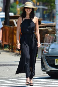 Olivia Munn goes boho in a gauzy black maxi from Calypso St. Barth with a Max Mara cross-body bag and floppy felt hat.   - HarpersBAZAAR.com
