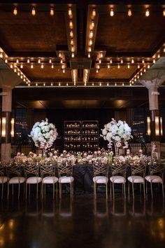 real wedding photo of houston wedding at the astorian landmark loft venue gold cross back chairs white flower arrangements black linen wedding table