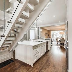 An open-concept white kitchen with a very large kitchen island. Glass staircase, warm hardwood floors. #kitchen #design #inspiration #whitekitchen #kitchenisland