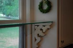 Kitchen window shelf held up with antique corbels. Jamie says: I love the idea of the glass shelf in the window for plants and stuff