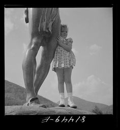 A little girl clinging to the bronze statue of an Indian on the Mohawk Trail in Massachusetts