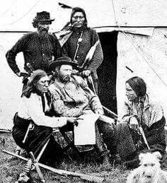 "George Armstrong Custer poses with his Indian scouts during the Black Hills expedition of 1874.  The man pointing at the map was named ""Bloody Knife"", a member of the Cree tribe.  Photo by William Illigworth."