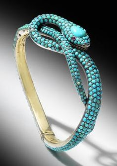 A Victorian turquoise snake hinged bangle, mid 19th century. The bangle set throughout with circular cabochon turquoise, the head decorated with a large pear-shaped cabochon turquoise and circular cabochon ruby eyes.