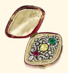 George III diamond, emerald and ruby brooch. The shield-shaped scrolling old-cut diamond panel mounted with a square-shaped emerald, a pear-shaped yellow diamond and a circular-cut ruby collet to the pear-shaped diamond detail, mounted in silver and gold, circa 1830, 5.0cm long, with fitted case. Sold by Christie's in 2011.