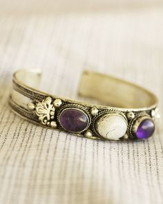 Bless your life with the radiant touch of moonstone, transcendent amethyst, and a Tibetan celestial cloud motif upon our silver-plated cuff bracelet from Nepal. Handmade in and fairly traded from Nepal.