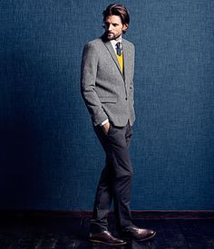 Grey jacket with black cravat over white, high collared shirt and mustard sweater. Navy slacks with mocha loafers.