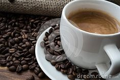 Coffee beans with cup of coffee on wooden table, brown, warm, shallow, detail