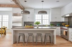 White and gray kitchen features white cabinets adorned with brushed brass pulls paired with gray quartz countertops and backsplash.