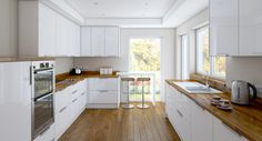 High Gloss White Kitchen, wooden worktops + floor. Ceramic sink?