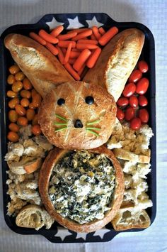 If you are looking for a cute addition to your Easter table, try out this Easter bunny bread filled with Spinach Artichoke dip and surrounded by cut veggies. You can use the veggies or the bread for dipping. Both taste great! Happy Easter! 1 loaf round boule style bread 1 loaf italian or french baguette style bread 1 batch of Spinach Artichoke Dip assorted veggies (I used baby carrots and red/yellow cherry tomatoes) black olives and celery, for garnish 1. Cut off the top circle of the round…