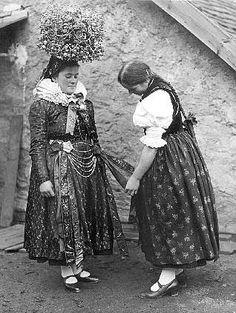 Junge Frau im traditionellen Brautschmuck, bestehend aus der großen Brautkrone (Schäpel), einem breiten Faltenkragen und Bändern an Hals und Gürtel.