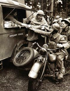 A motorcyclist of the 1st Canadian Reconnaissance Squadron enjoys a cup of tea during an interlude in the days work. Behind him can be seen a Lewis machine gun of the First World War - UK -1940