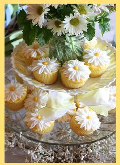 Daisies in mason jar surrounded by decorated cupcakes. Adorable centerpiece!