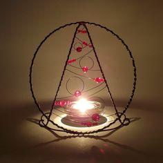 """Stromeček+Drátovaný+vánoční+stromeček+(+svícen+)+z+černého+žíhaného+drátu+dozdobený+skleněnými+korálky+v+červené+barvě+(+různé+odstíny+).+Korálky+obkroužené+drátem+jsou+napevno+přidrátované,+ostatní+korálky+jsou+posuvné.+Čirý+skleněný+svícen+je+součástí+výrobku.+Stromeček+je+zamýšlen+jako+dekorační+""""+stínítko+""""+pro+čajovou+svíčku.+Rozměry+:..."""