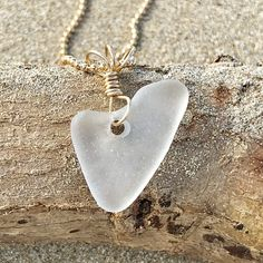 "A near FLAWLESS heart is a RARE find in the world of authentic, surf tumbled beach sea glass. This is a perfectly smooth, white genuine sea glass heart. From years of tumbling in the ocean, it has a hint of sparkle to it. Decorated with a handcrafted gold filled wire wrapped bail, it hangs from a 17"" diamond cut bead b"
