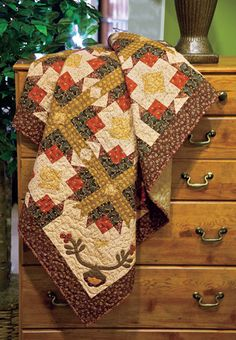 Tulip Twist: Traditional hand applique enhances classic pieced throw. Designed by Deanne Eisenman, snugglesquilts.com. Repin this image for a chance to win a copy of this issue!