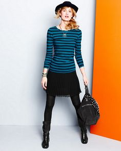 Striped top with pleated black skirt, tights and black boots.