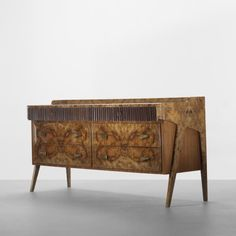 Gio Ponti cabinet Casa e Giardino Italy, c. 1940 maple burl, lacquered mahogany, reverse-painted glass, Italian walnut, brass 69 w x 20.25 d x 33.25 h inches  Cabinet features six drawers, two of which are locking. Sold with certificate of authenticity from the Gio Ponti Archives.  Provenance: Important private collection  Estimate: $20,000–30,000 Result: $21,250