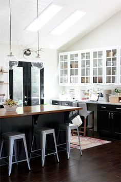 A white kitchen with lofty ceilings is grounded by base cabinets, kitchen-island cabinets, and glossy doors in black. Via @remodelista