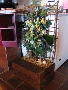 Decoratie met kunstbloemen en vers blad. Gemaakt op een zelf gevlochten raamwerk. Voor restaurant Taverne de Kade in Grou.