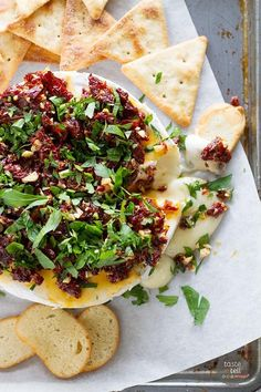 Brie is topped with sun-dried tomatoes, garlic and parsley in this easy appetizer that takes minutes to throw together.