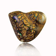 This very unusual intricately patterned solid sandstone matrix Opal from Yowah, Queensland has brilliant flashes of green blue & purple – a unique stone.