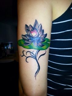 Lotus growing through a lily pad , coming up from water . Meaning : (overcoming a hard time in life)