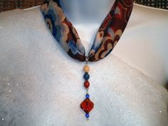 The scarf is a pretty combination of white, ivory, rust, brown and two shades of blue in an abstract flower pattern. The top of the dangle contains 3 nuggets in ivory, navy and rust - separated by silver spacers. The second part is made up of a curved brown glass bead surrounded