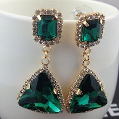 These stunning earrings feature a stud with a cushion cut emerald colored stone surrounded by white cz diamond stones, with a large dangling triangle-shaped sto