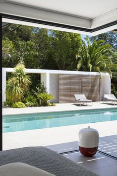 sensación exterior: piscina con pavimento de la terraza en tonos claros, porche/living en blanco y toques de madera como la casa, vegetación tropical