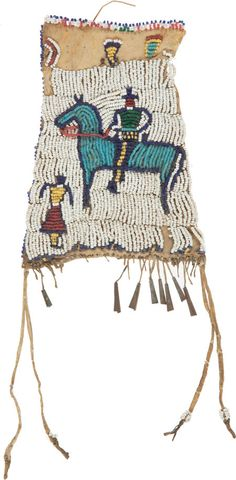 """Indian Wars, Old Plains Indian Medicine Pouch With Figural Decoration...Plains Indian pouch featuring beadwork depicting a figure riding a light blue horse and standing female figure. The equestrian figure appears to be a soldier with tall blue campaign hat and blue trousers with yellow stripe. Pouch measures 6 1/2"""" long without the tassels and 5"""" wide at the base. Sinew sewn beads with a """"lazy"""" stitch. Leather is stiff, missing most of its tin cone danglers, plain back."""