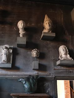 Art Gallery Wall, antique bust, terra cotta and marble statues, charcoal gray walls.