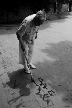 Fading - Old man painting chinese calligraphy in water