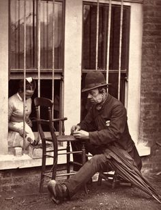"""Street Life in London"" by John Thomson (1876): Caney the Clown -  ""thousands remember how he delighted them with his string of sausages at the yearly pantomime, but Caney has cut his last caper since his exertions to please at Stepney Fair caused the bursting of a varicose vein in his leg and, although his careworn face fails to reflect his natural joviality, the mending of chairs brings him constant employment."""