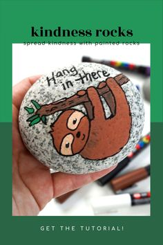"""Learn how to paint a sloth with paint pens. This sloth painted rock is perfect for beginners. Use this rock painting idea to hide around your town, give as a gift, or decorate your home. Add the phrase """"Hang In There"""" to create a cute kindness rock. #sloth #paintpens #paintedrocks #rockpainting101"""