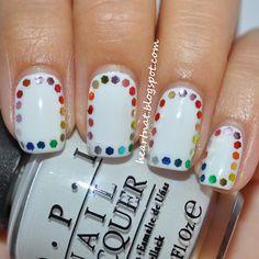 Rainbow polka dot manicure with glitter bits on white polish