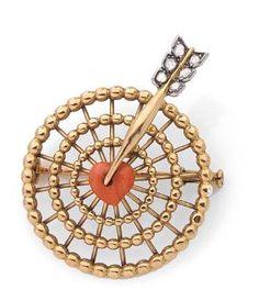 CARTIER ANNÉES 1950 Broche «cible» en fil torsadé d'or jaune 18K, le Yves Saint Laurent piqué d'un coeur en corail, les ailettes de la flèche soulignées de petits diamants taillés en roses. Signée et numérotée… - Pierre Bergé & associés - 18/11/2015