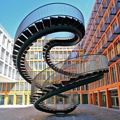 "This steel staircase sculpture titled ""Umschreibung"" is a wonderful piece of art designed by Olafur Eliasson. This beautiful merging of art and architecture is a 9 meter-high walk-double spiral of steel in the entrance of the KPMG ( a global accounting firm ) office building in Munich, Germany."