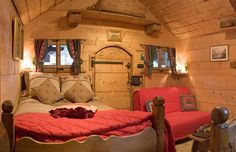 cabin with scalloped frame wood bed and tiny windows