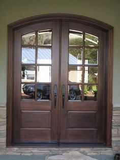 Interior. double glass front doors with dark brown wooden frame placed on the…