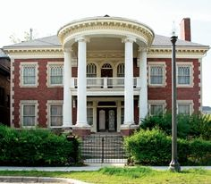 This is a neoclassical house because it has symmetrical shapes and tall colomns that rise the full height of the building .