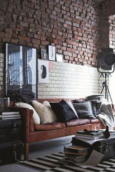 decoração sala de estar no estilo industrial com sofá de couro marrom, almofadas em tons neutros, parede rústica de tijolos aparecendo