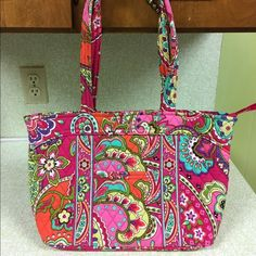 Vera Bradley Pink Swirls Travel Tote Nice bag. Bright colors. No fading. Some soiling on the straps. I've taken pictures of both sides. One side has more soiling than the other. Rest of the bag in perfect condition. No wear on bottom. Strap drop 11 inches. 15 inches long. 4.75 wide. 10 inches tall. One outside pocket. 6 pockets in the inside. Vera Bradley Bags Totes