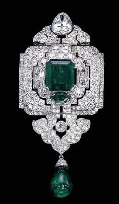 An emerald and diamond pendant-brooch, by Cartier. Designed as an old European and old mine-cut diamond openwork panel with a central rectangular-cut emerald weighing 12.28 carats, suspending a diamond palmette and emerald bead drop, to the pear-shaped diamond surmount,circa 1927,